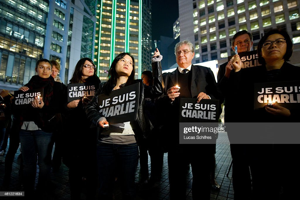 Journalists and citizens hold pens up during a vigil organized by the International Federation of Journalists led by its manager Serenade L. W. Woo (fourth from left) for the victims of the terrorist attack on 'Charlie Hebdo' in Paris, at the Statue Square on January 9, 2015 in Hong Kong, Hong Kong. Twelve people were killed on January 7 including two police officers as two gunmen opened fire at the offices of the French satirical publication Charlie Hebdo.