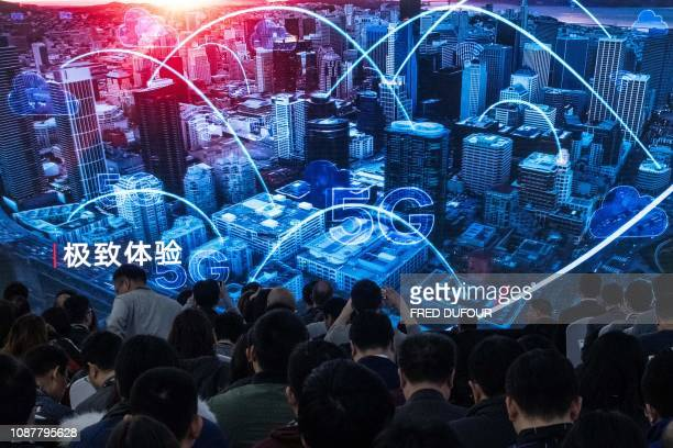 Journalists and guests watch a trailer during a press conference and launch of new 5G Huawei products at the Huawei Beijing Executive Briefing Centre...