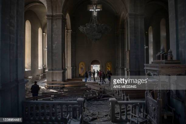 Journalists and local inhabitants stand on October 8, 2020 inside the damaged Ghazanchetsots Cathedral in the historic city of Shusha, some 15...