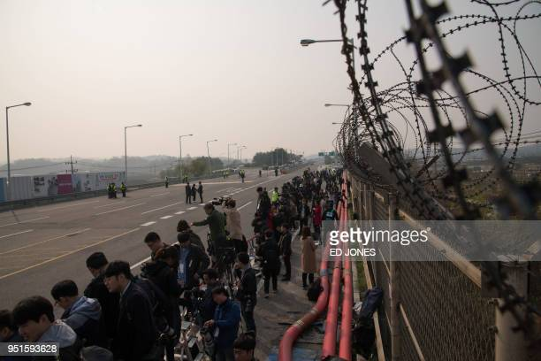 TOPSHOT Journalists and media stand on Tongil bridge before a checkpoint as they wait for the convoy carrying South Korean president Moon Jaein...
