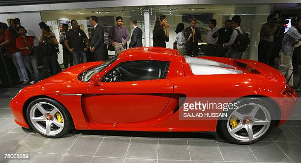 Journalists and officials stand next to the Carerra GT sports car at the Porsche centre in Mumbai 20 November 2007 German luxury sports car maker...