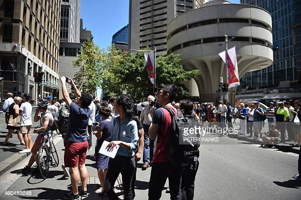 Journalists and onlookers gather in Martin Place in the central business district of Sydney on December 15 2014 A gunman was holding terrified...