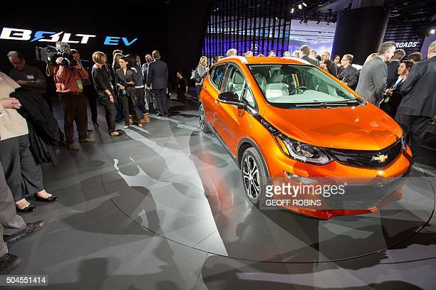 Journalists and photographers gather around the 2017 Chevrolet Bolt following the Chevrolet press conference at the 2016 North American International...