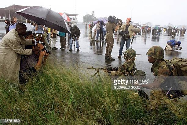 Journalists and photographers work as soldiers from the ECOWAS take position 04 August 2003 upon their arrival at Robertsfield airport near Monrovia...