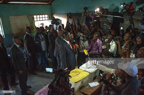 Journalists and polling staff look on as Kenya's Prime Minister Raila Odinga candidate for the country's presidency addresses the media after voting...