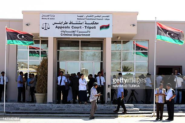 Journalists and security guards stand outside the Appeals Court in Tripoli during the trial of former Libyan foreign intelligence chief Bouzid Dorda...