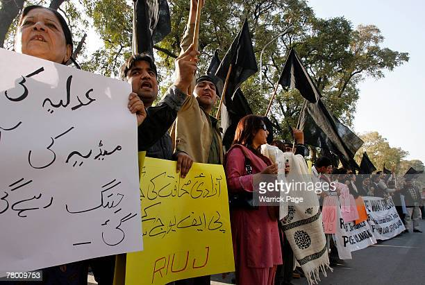 Journalists and their supporters hold banners and wave black flags during a protest against media restrictions outside the Islamabad Press Club on...