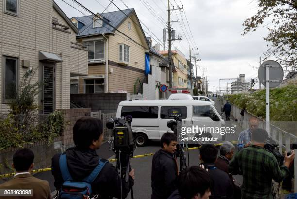 Journalists and TV camerapersons beside an apartment where Japanese police found nine bodies including two with their heads severed and dumped in a...