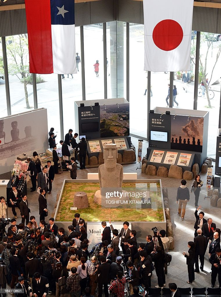 Journalists and visitors gather to see the new 'Moai' statue, modelled on the mysterious carvings at Easter Island, presented to the tsunami-devastated town of Minamisanriku during its preview in Tokyo on March 20, 2013. The giant present rossed the ocean from Chile as the town's original was destroyed in the March 11 quake-sparked tsunami disaster in 2011.