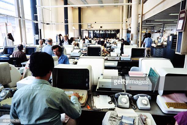 Journalists are seen working on computers in the press room of French press agency Agence FrancePresse in Paris August 1980
