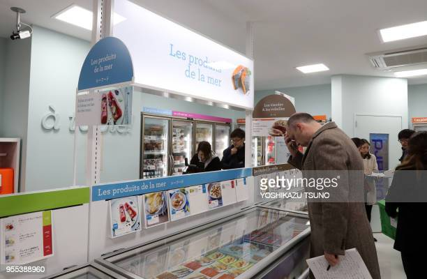 Journalists check frozen foods at a press preview of French food giant Picard's first shop in Tokyo on November 21 2016 Picard and Japan's largest...