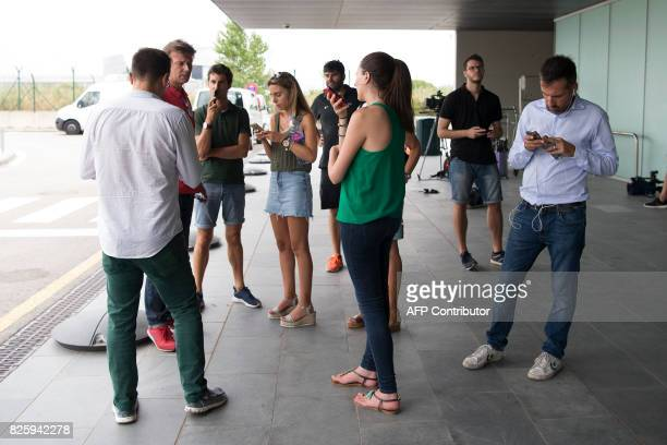 Journalists check their mobile phones as they wait for the arrival of Brazilian forward Neymar outside Barcelona's airport in Barcelona on August 3...