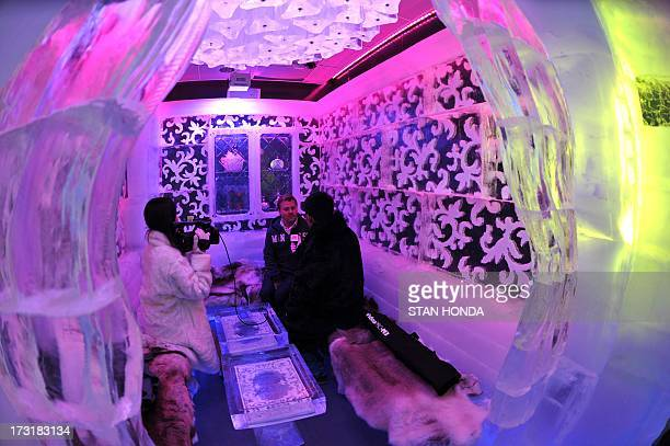Journalists conduct an interview in a room in the Minus 5 Ice Bar during a preview at the New York Hilton Midtown Hotel July 9 2013 in New York The...