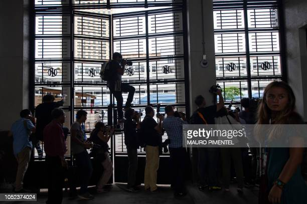 Journalists cover Brazilian farright presidential candidate Jair Bolsonaro's visit to the Federal Police station in Rio de Janeiro Brazil on October...