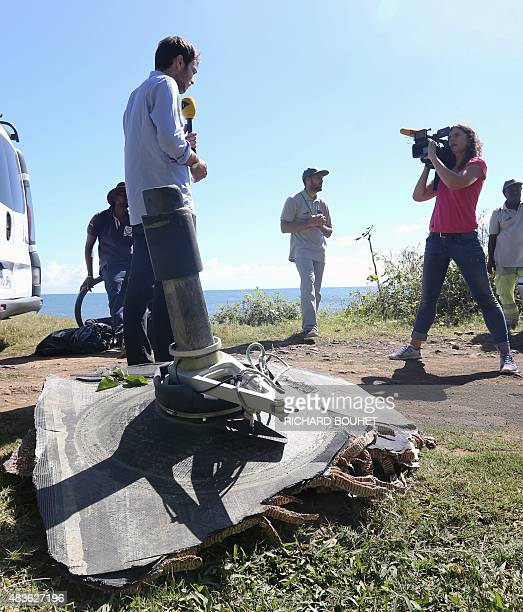 Journalists cover the hunt for wreckage on August 11 2015 in the eastern part of SainteSuzanne on France's Reunion Island in the Indian Ocean during...