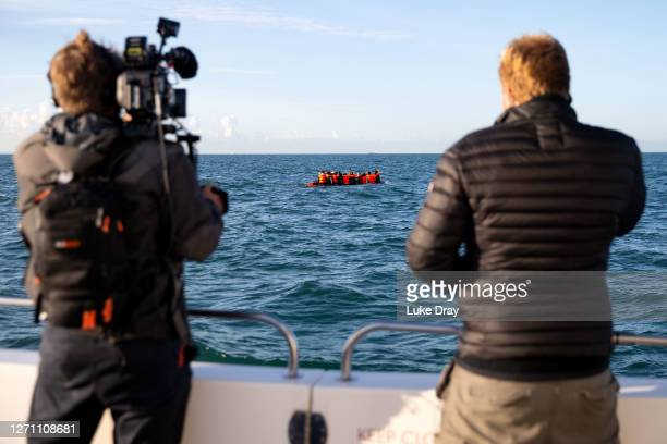 Journalists document a group migrants packed tightly onto a small inflatable boat attempt to cross the English Channel near the Dover Strait, the...