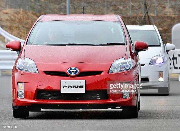 Journalists drive prototypes of Toyota's new hybrid vehicle Prius during a test drive event at Fuji Speedway in Oyama, 100km west of Tokyo, on March...