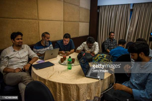 Journalists edit their stories and pictures on their personal laptops before filing on the only internet line connected with four computers at a...