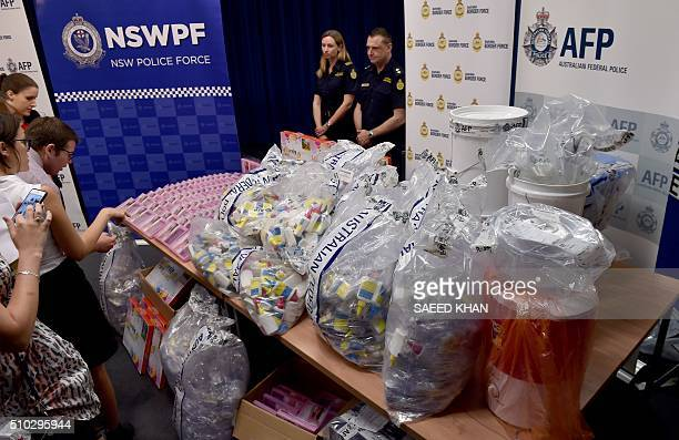 Journalists examine a haul of crystal methamphetamine concealed in packaging at the Australian Federal Police headquarters in Sydney on February 15...