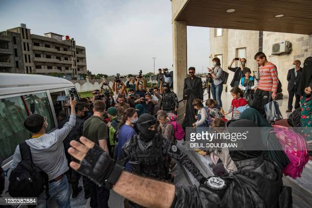 Journalists film as children prepare to board a bus during the handover of orphaned children, whose parents were suspected of belonging to the...