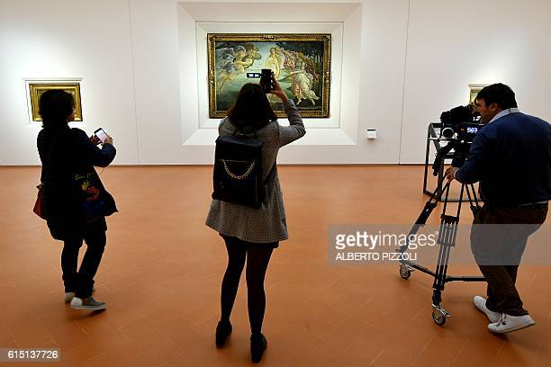 Journalists film 'The birth of Venus' painted in the mid 1480s by Italian painter Sandro Botticelli during a press preview for the reopening of the...