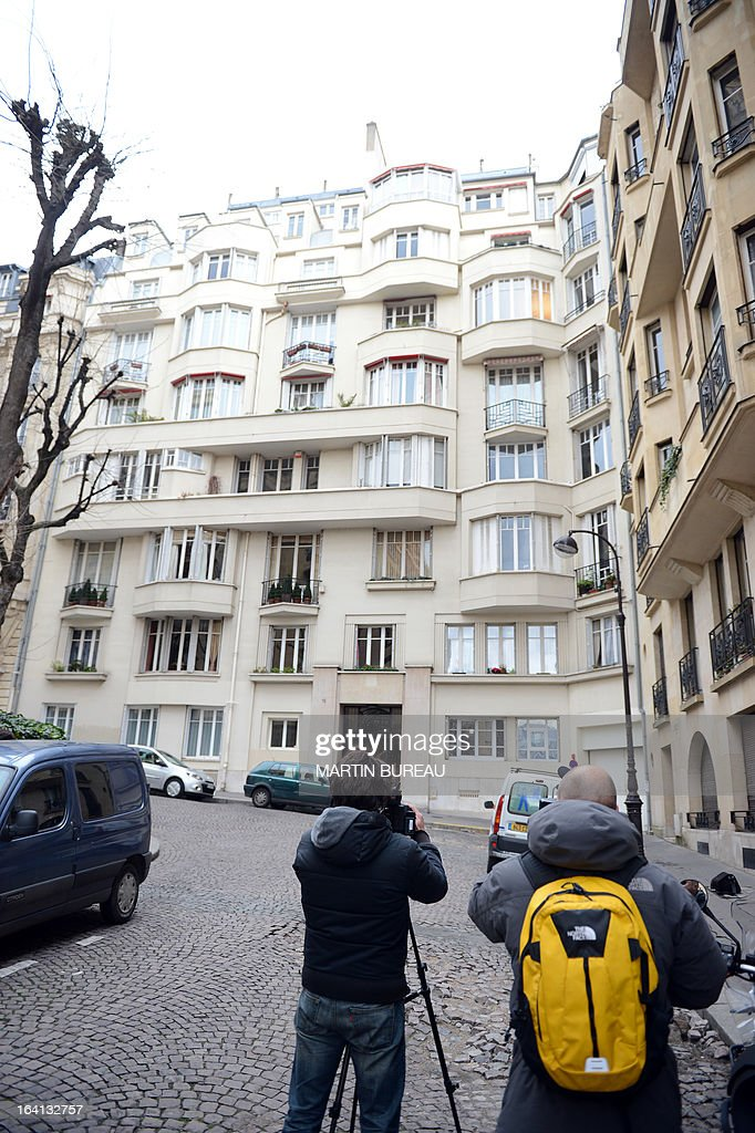 Journalists film the building where live IMF chief and former French Finance Minister Christine Lagarde, on March 20, 2013 in Paris, during a search by French police at her home, in connection with a probe into her handling of a high-profile scandal when she was a government minister. The investigation concerns Lagarde's 2007 decision to order a panel of judges to arbitrate on the fallout from a dispute between disgraced tycoon Bernard Tapie and the collapsed bank Credit Lyonnais. The arbitration resulted in Tapie being awarded around 400 million euros ($500m).