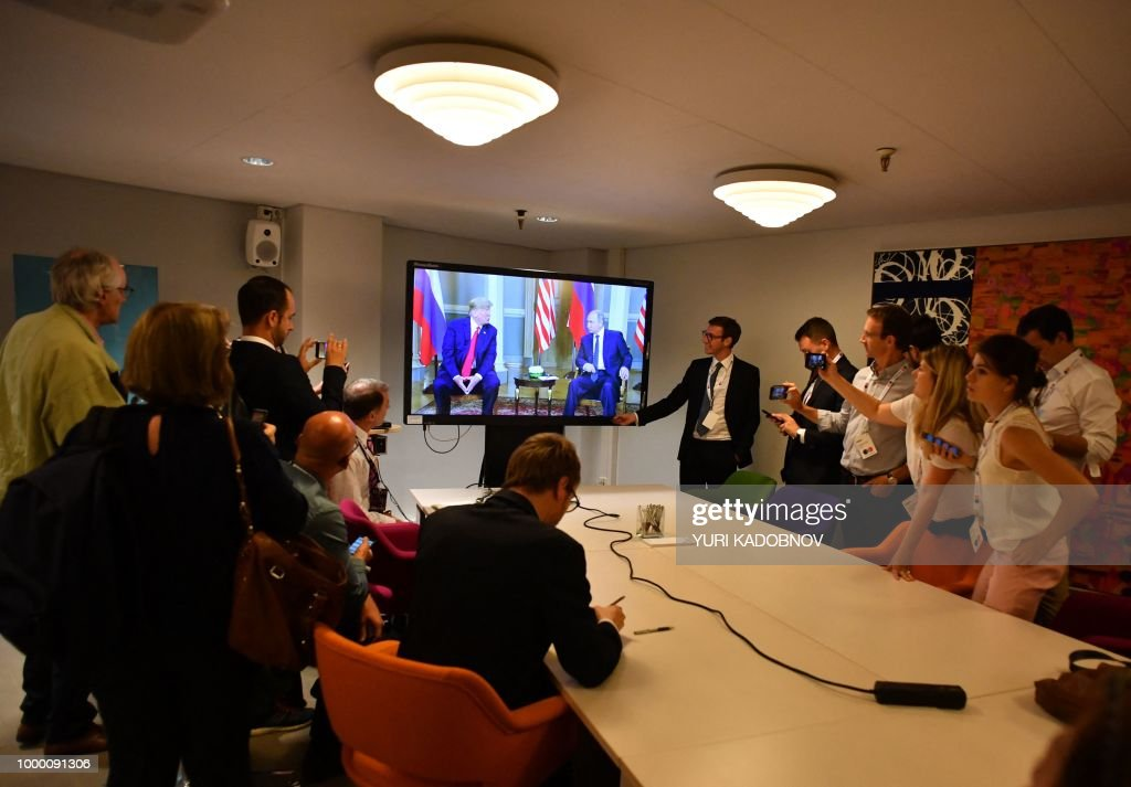 TOPSHOT - Journalists follow the meeting of Russian President Vladimir Putin (Center R) and US President Donald Trump on a dipsplay, in Helsinki, on July 16, 2018.