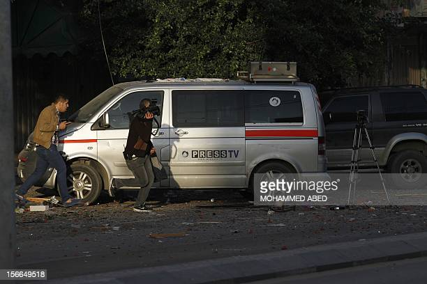 Journalists from different agencys run past press vehicles on a road after an Israeli air strike on an office of Hamas television channel AlAqsa in...