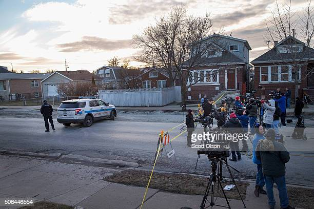 Journalists gather at the perimeter of a crime scene where six people were found slain inside a home on the city's Southwest Side on February 4 2016...