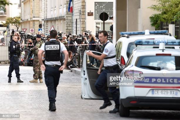Journalists gather behind a cordon as police work at the site where a car slammed into soldiers in LevalloisPerret outside Paris on August 9 2017...