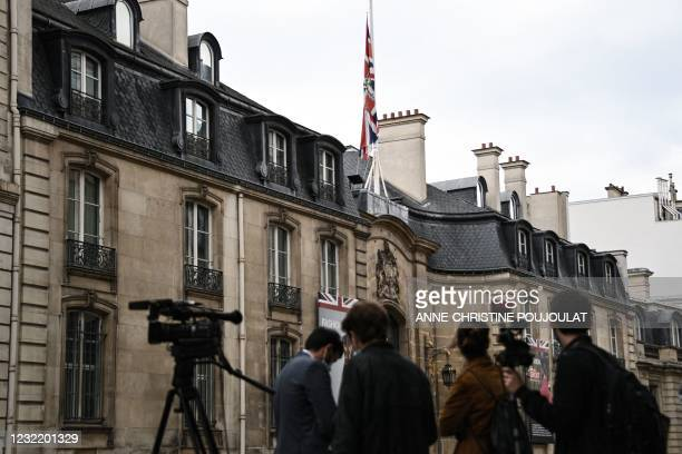 Journalists gather in front of the British Embassy where the Britain's national flag, the Union Jack, flies at half-mast, in Paris on April 9, 2021...