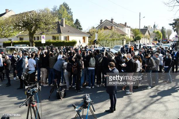 Journalists gather near the site where a female police employee was stabbed to death by a Tunisian man at a police station, southwest of Paris in...