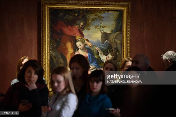 Journalists gather next to the painting 'Rest on the Flight into Egypt' by Federico Fiori known as Federico Barocci during a press preview of the...