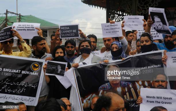 Journalists hold placards during a protest against the assassination of veteran journalist and EditorinChief of Daily Rising Kashmir Syed Shujaat...