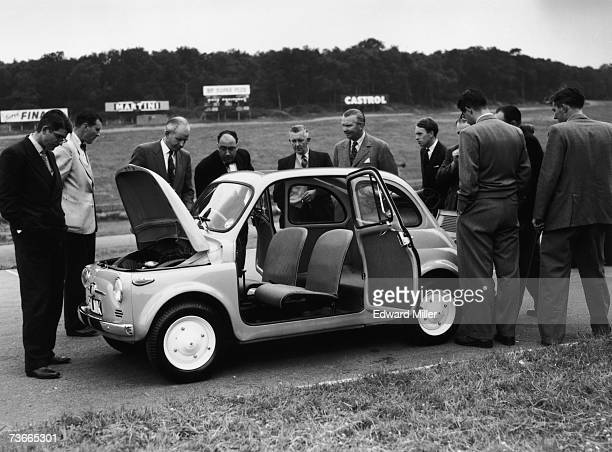 Journalists inspect the new Fiat 500 economy car at Brands Hatch racing circuit Kent 29th July 1957 The car is powered by a 479cc aircooled engine...