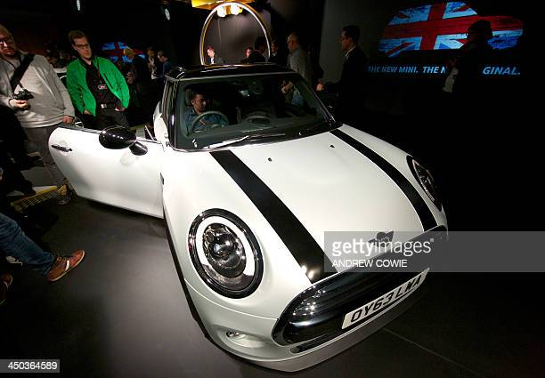 Journalists inspect the new Mini Cooper during its official unveiling at BMW's plant at Cowley in Oxford central England on November 18 2013 Car...