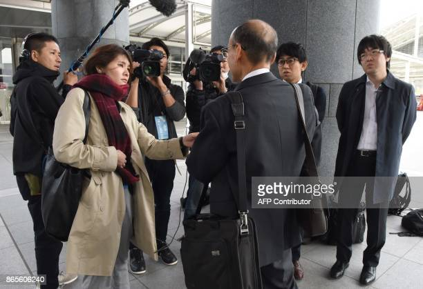Journalists interview a shareholdetr before an extraordinary shareholders meeting of Toshiba in Chiba suburb of Tokyo on October 24 2017 Toshiba's...