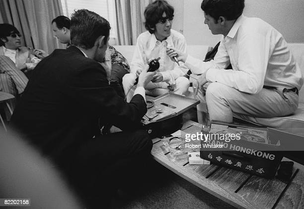 Journalists interview George Harrison and John Lennon in the VIP lounge at Kaitak Airport Hong Kong as the Beatles wait for a connecting flight to...
