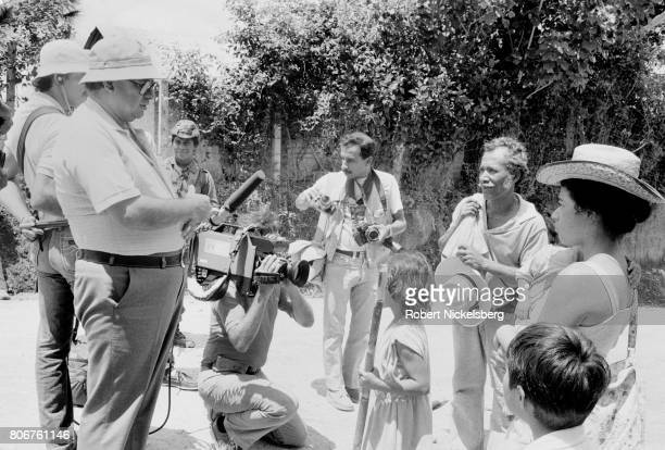 Journalists interview local residents as they move their belongings before an assault by the Atlacatl Battalion as soldiers advance during a military...