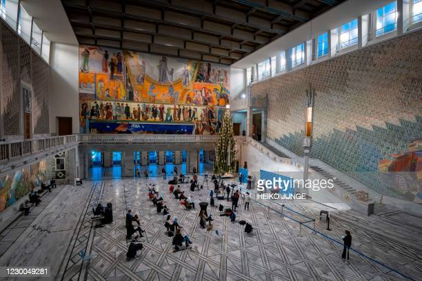 Journalists keep distance as they attend a press conference on December 10, 2020 in Oslo City Hall, as informations are given about new corona...