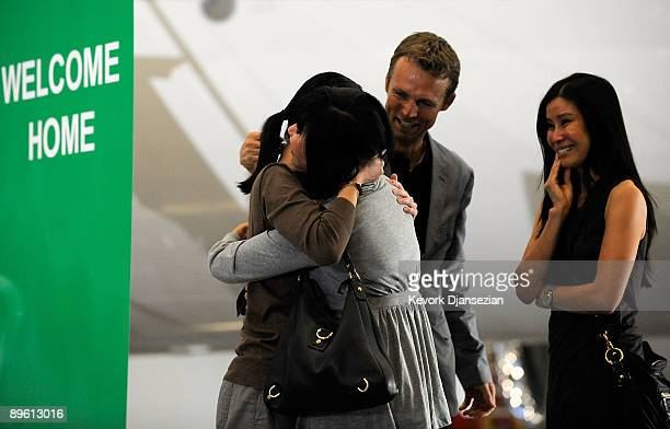 Journalists Laura Ling hugs her mother Mary Ling as they stand with sister Lisa Ling and Iain Clayton as Laura Ling and Euna Lee arrive at Hangar 25...