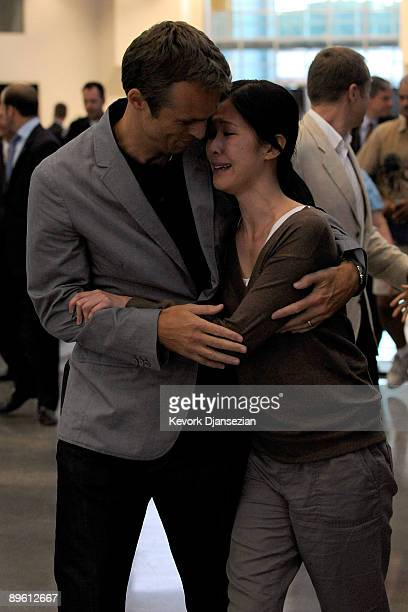 Journalists Laura Ling hugs husband Iain Clayton as Ling arrives with Euna Lee at Hangar 25 on August 5, 2009 in Burbank, California after being...