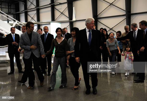 Journalists Laura Ling, husband Iain Clayton and mother Mary Ling walk with former President Bill Clinton as Ling arrives with Euna Lee who is...
