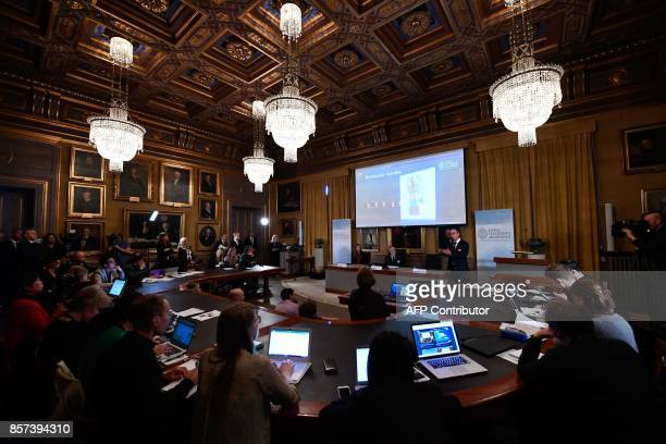 Journalists listen to members of the Nobel Committee Sara Snogerup Linse the Secretary General of the Royal Swedish Academy of Sciences Goran Hansson...