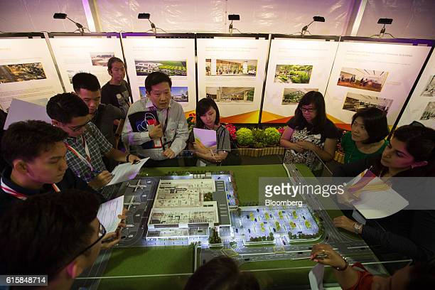 Journalists look at a model of Seletar Airport's new passenger terminal during a groundbreaking ceremony in Singapore on Thursday Oct 20 2016 The...