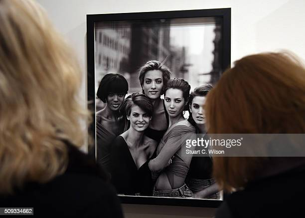 Journalists look at a photo of famous models at the press preview for 'Vogue 100 A Century of Style' exhibiting the photographs that has been...