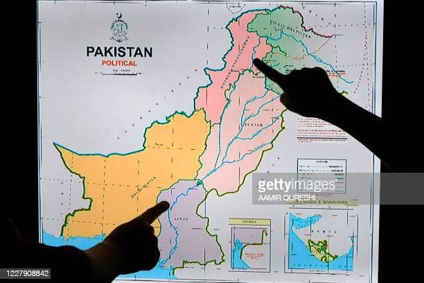 Journalists look at Pakistan's new political map on a screen at the Daily Metro Watch newspaper offices in Islamabad on August 4 2020 Pakistan's...