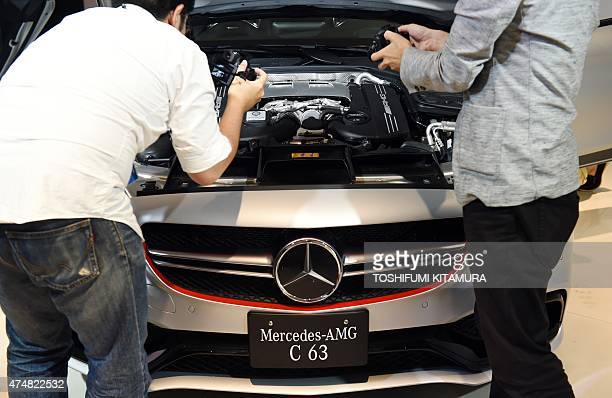 Journalists look at the engine of new MercedesAMG C63 S Edition 1 during its press preview in Tokyo on May 27 2015 MercedesBenz Japan will receive...