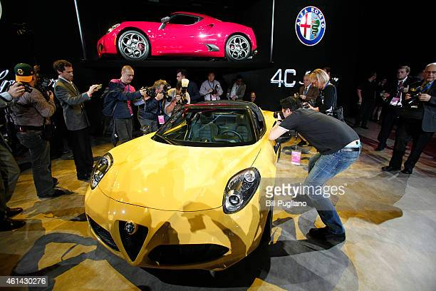 Journalists look at the new 2015 Alfa Romeo 4C Spider convertible after it was revealed to the media at the 2015 North American International Auto...
