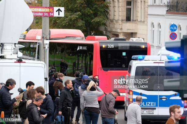 Journalists look on as members of the Jewish community are driven away in a bus from the synagogue after a shooting in Halle an der Saale eastern...